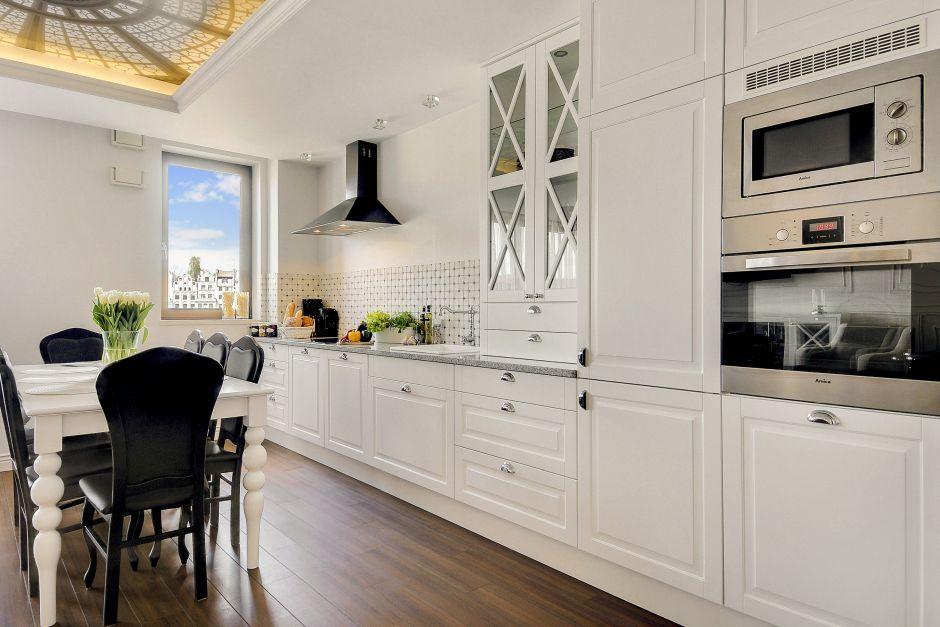 Białe meble w stylu angielskim w kuchni z ciemnym drewnem na podłodze