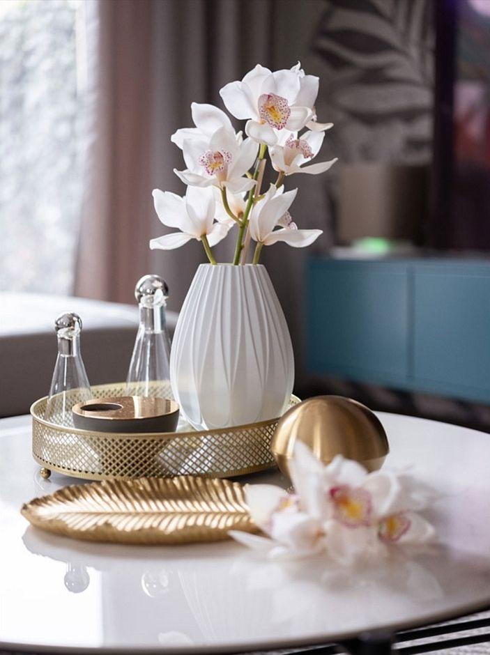 Akcesoria dekoracyjne w kolorze złota na stoliku w salonie