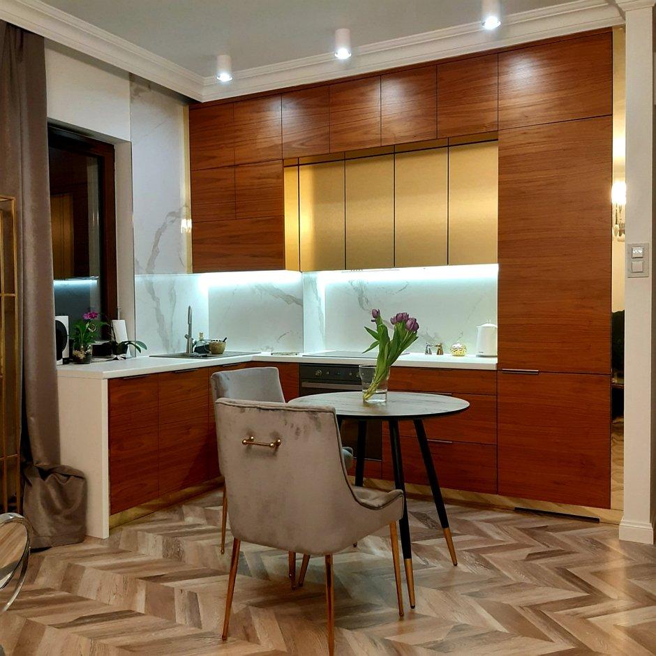 Aranżacja kuchni w kształcie litery L z marmurem, złotem i drewnem