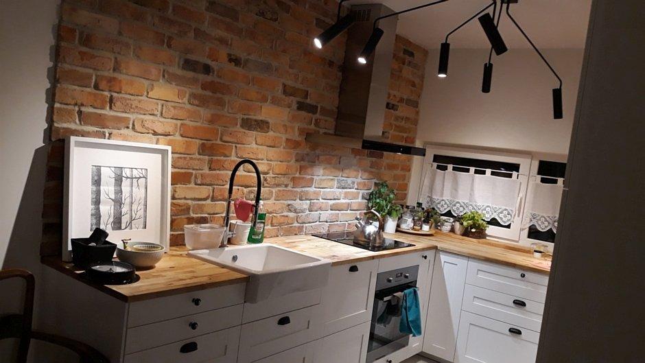 Aranżacja kuchni z białymi meblami i drewnianym blatem