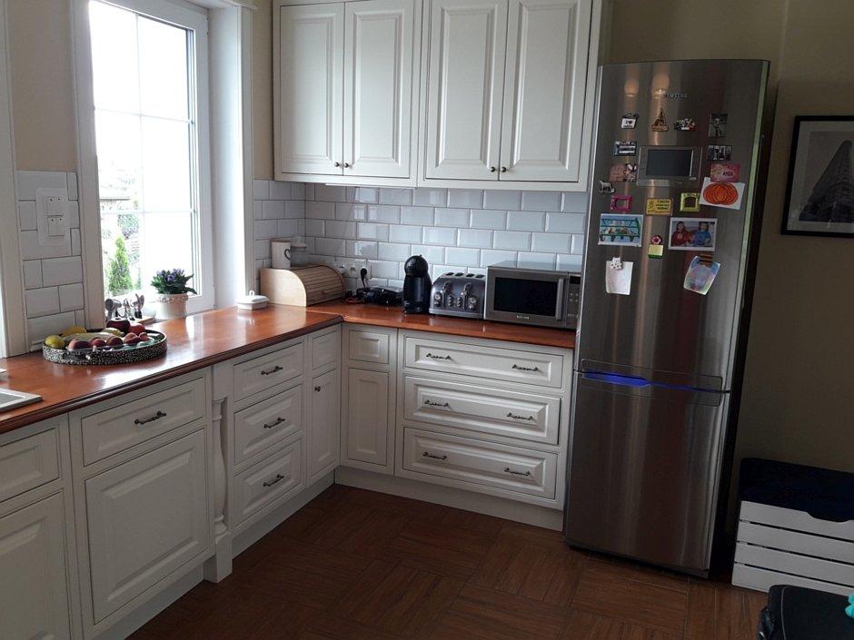 Aranżacja kuchni z białymi szafkami i srebrną lodówką