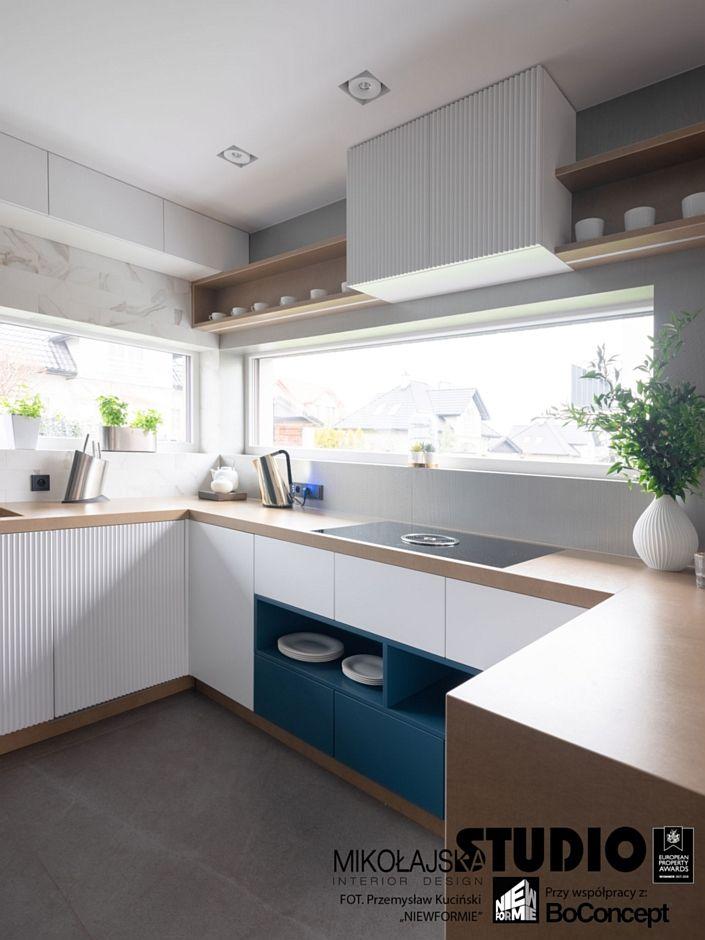 Aranżacja kuchni z szafkami bezuchwytowymi i okapem blatowym
