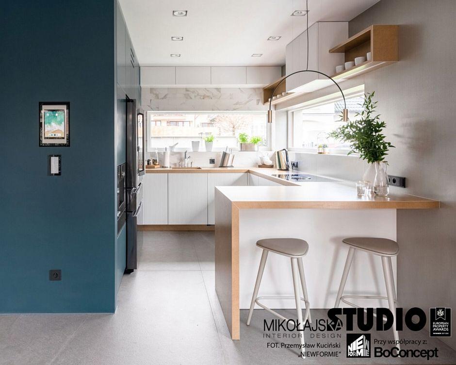 Aranżacja otwartej kuchni w kolorach drewna, bieli i błękitu z półwyspem