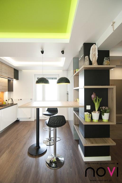 Barek kuchenny pomiędzy pokojem dziennym a kuchnią z czarnymi hokerami