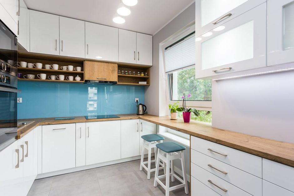 Białe drewniane hokery z miętowym siedziskiem w aranżacji kuchni