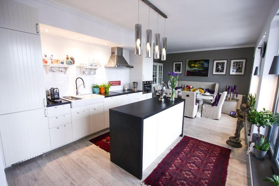 Białe meble kuchenne czarne blaty drewno na podłodze