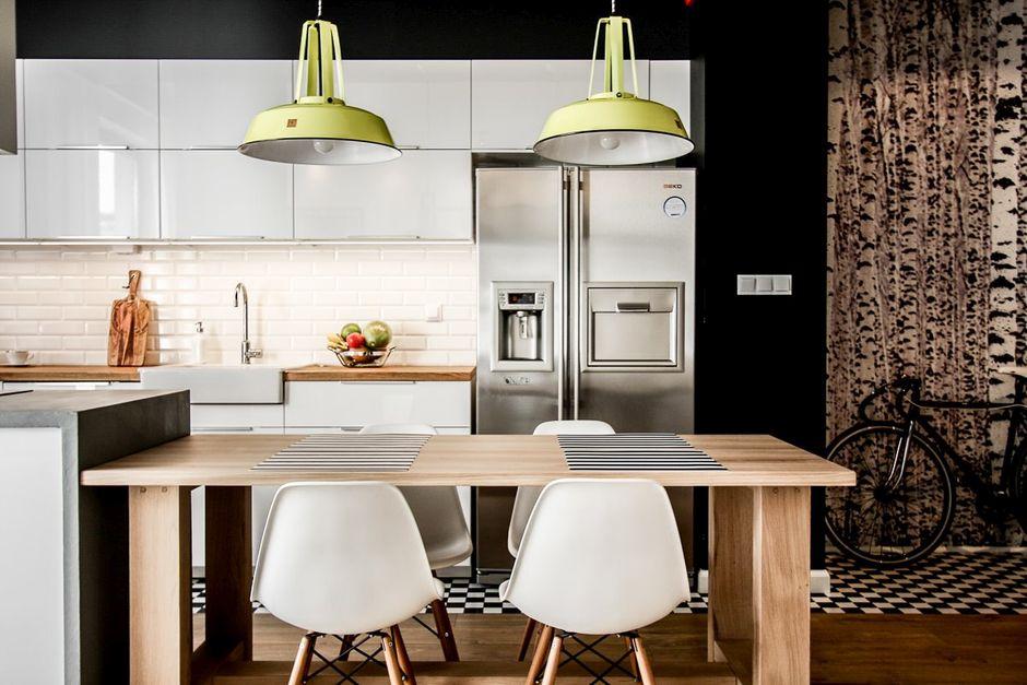 Białe plastikowe krzesła na drewnianych nogach w kuchni połączonej z jadalnią