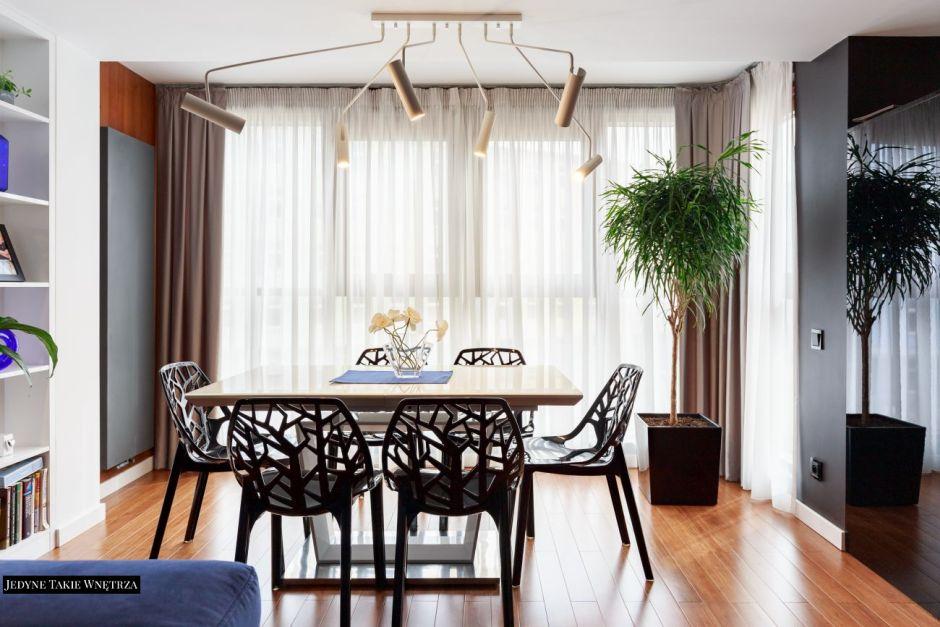 Czarne krzesła Arbor przy stole w jadalni połączonej z kuchnią