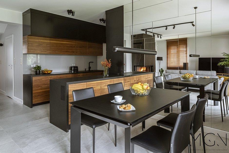 Czarne krzesła w jadalni połączonej z kuchnią
