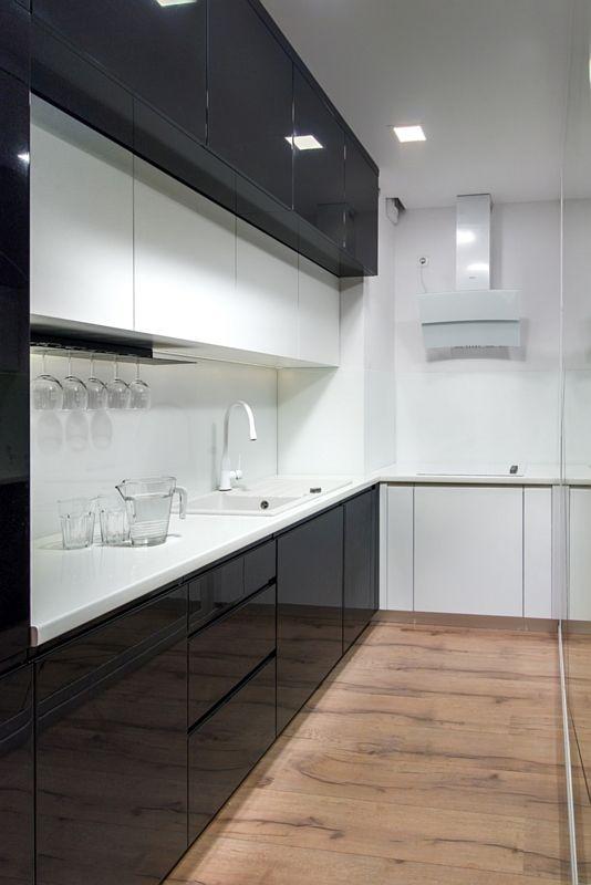 Drewniana podłoga w wąskiej biało-czarnej kuchni