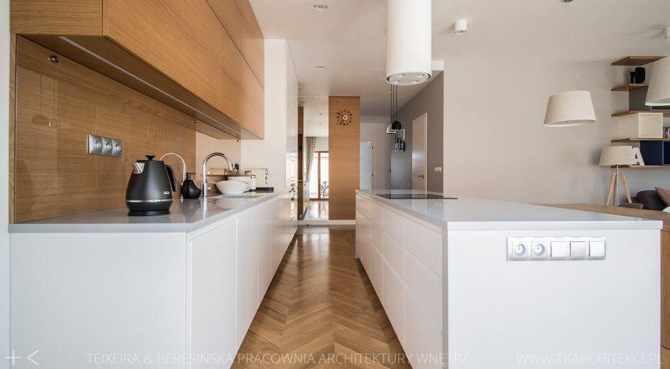 Drewniane płytki ułożone w jodełkę na podłodze w kuchni z białą wyspą