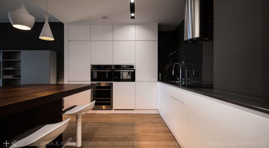 Drewno na podłodze w kuchni z białymi szafkami