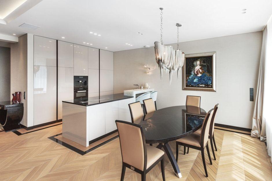 Drewno ułożone w jodełkę na podłodze w eleganckiej kuchni połączonej z jadalnią