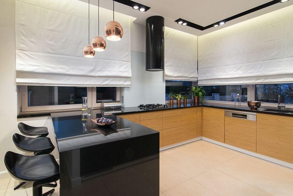 Duże beżowe płytki na podłodze w kuchni z czarnym półwyspem