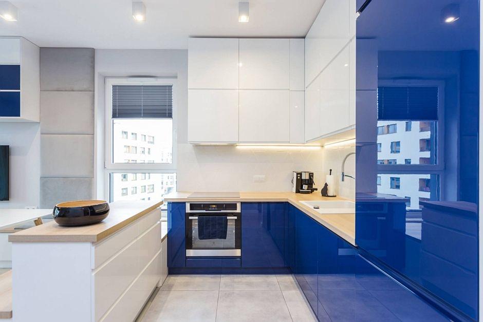 Kamienne płytki na podłodze w wąskiej kuchni z niebieskimi szafkami