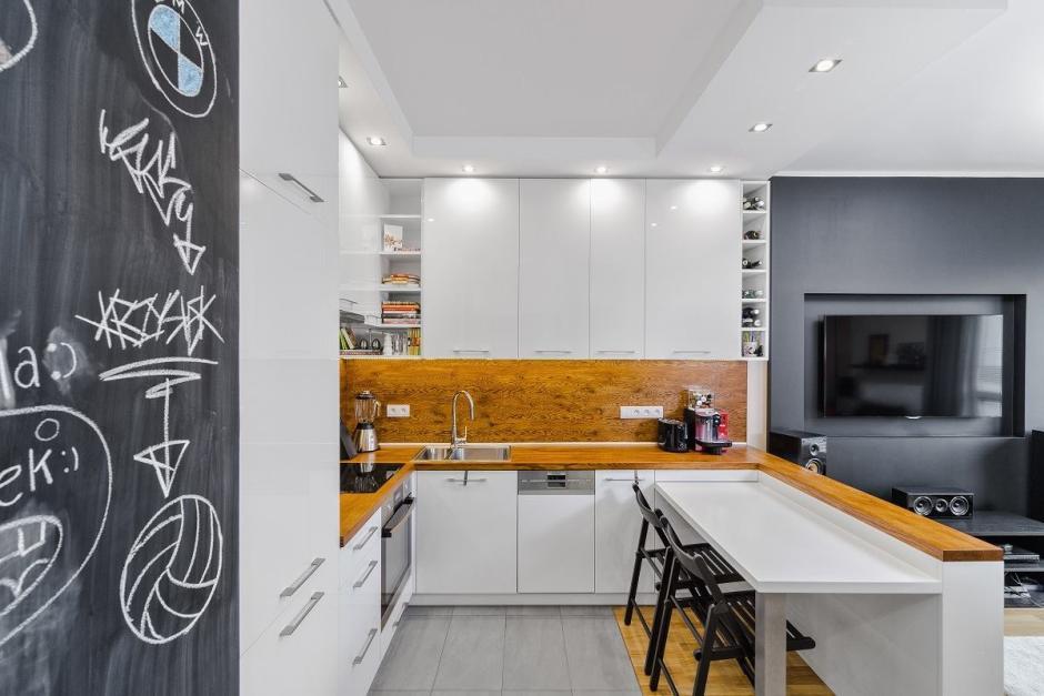 Kuchnia w kolorach bieli, czerni i drewna z półką na książki