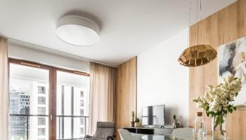 Drewniana wisząca lampa nad stołem w jadalni