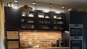Czarna zabudowa kuchni z cegłą