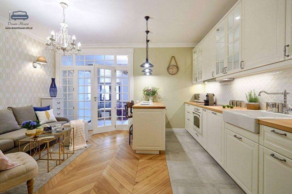 Płytki i drewno na podłodze w kuchni połączonej z salonem