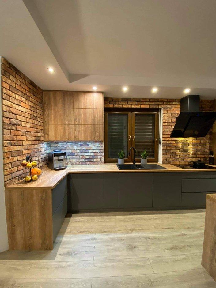 Kuchnia z podwieszanym sufitem i cegłą na ścianie