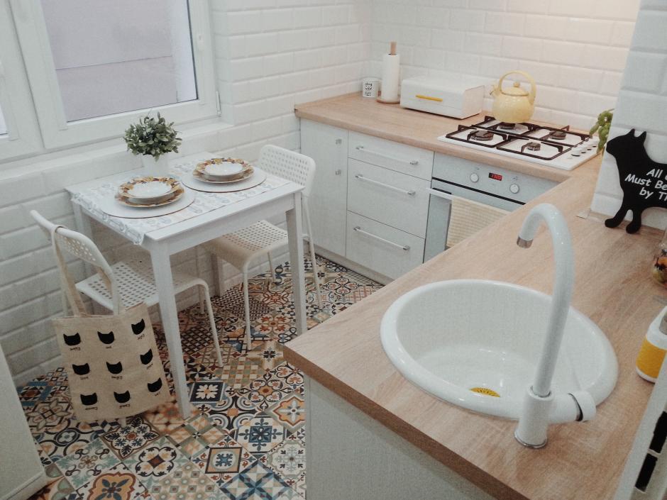 Połączenie bieli drewna i kolorowego patchworku w małej kuchni