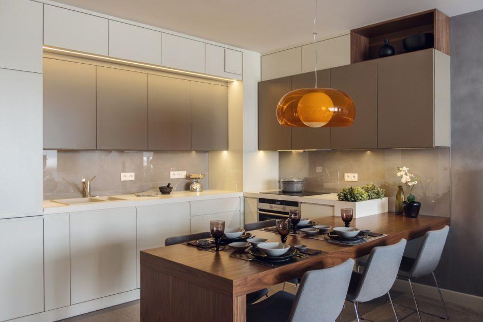 Pomarańczowa Lampa Wisząca Nad Drewnianym Półwyspem W Kuchni