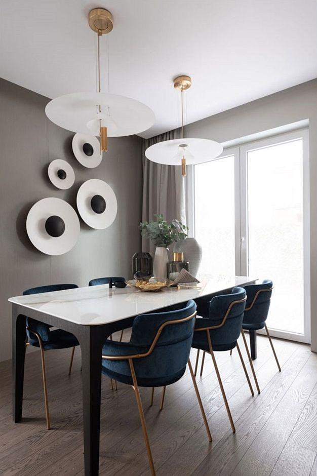 Stół z marmurowym blatem oraz oświetlnie w kolorze bieli i złota w aranżacji jadalni