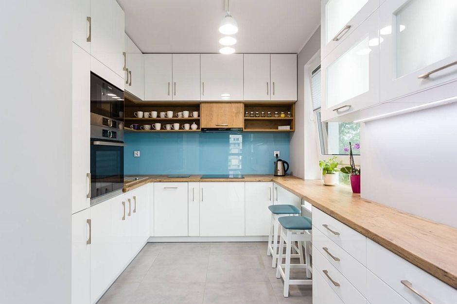 Szara podłoga w kuchni z białymi meblami