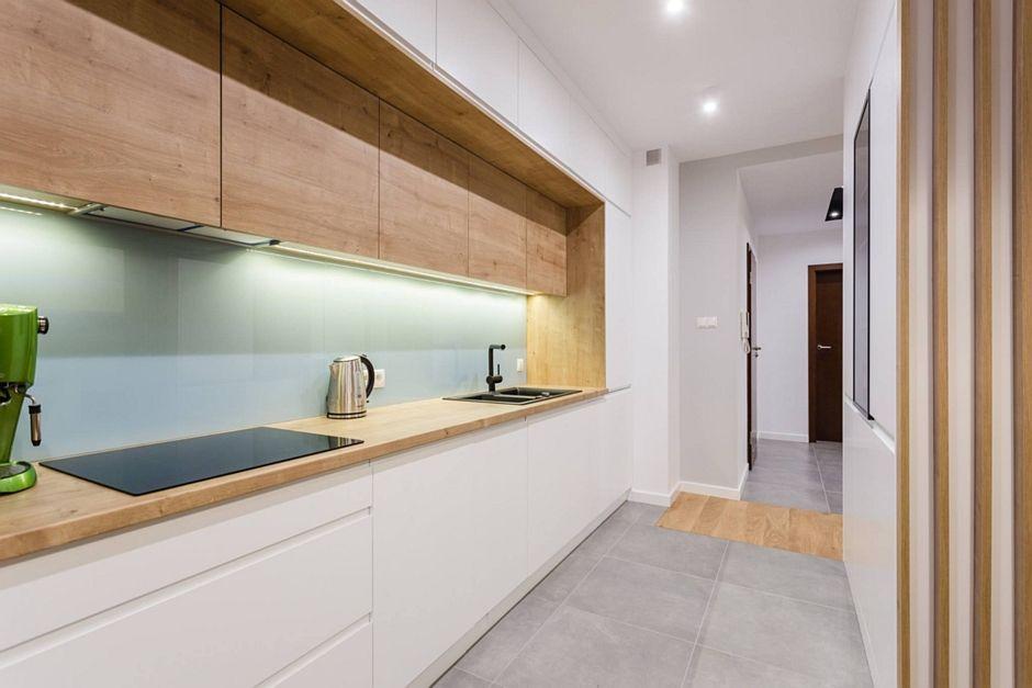Szare płytki na podłodze w kuchni z drewnianymi szafkami