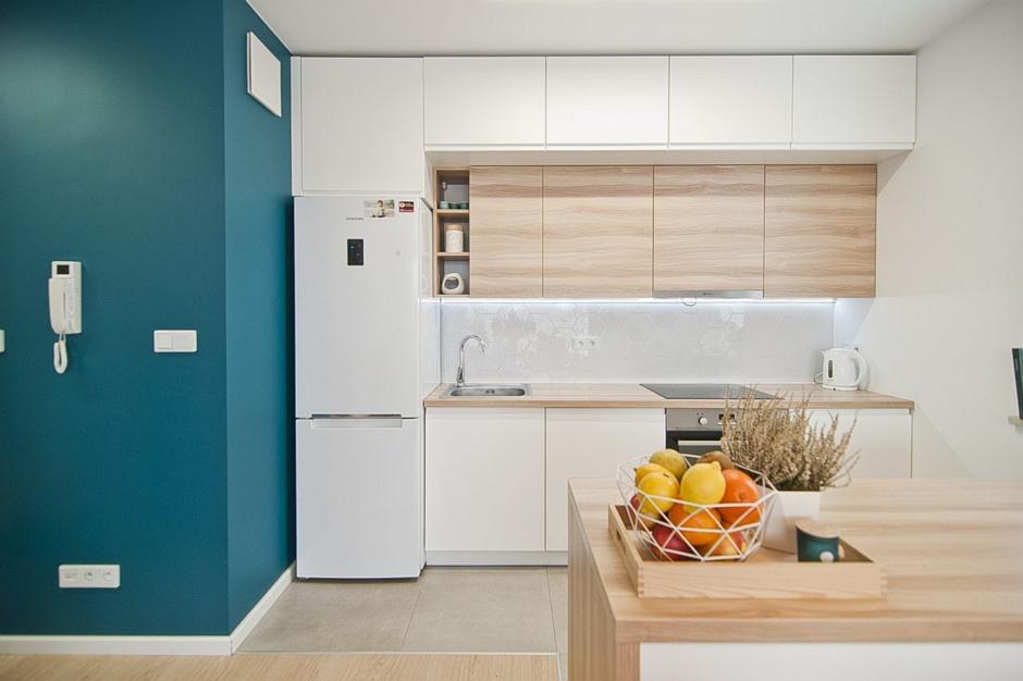 Wysoka zabudowa kuchni w kolorze drewna i bieli