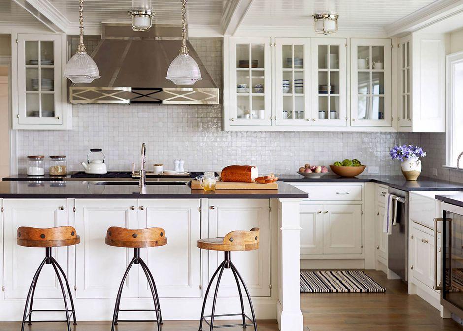 Drewniane siedziska metalowych hokerów w kuchni z dużym okapem