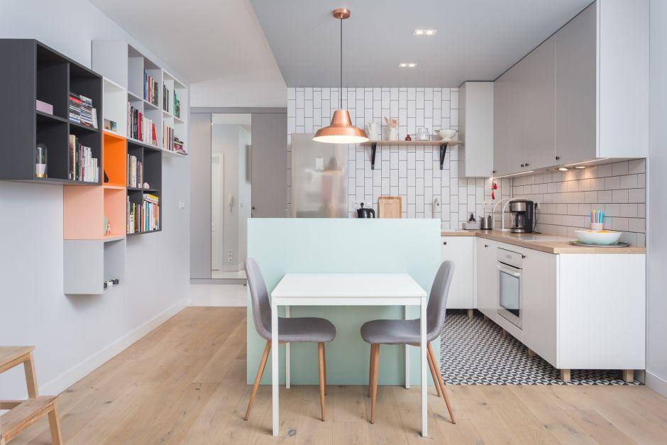Industrialna metalowa lampa nad stołem w jadalni połączonej z kuchnią