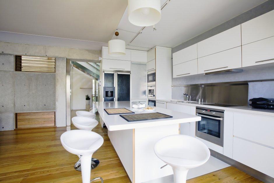 Biała zabudowa kuchenna z betonem na ścianie
